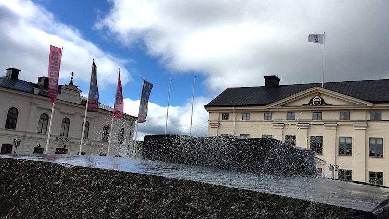 Närbild på fontänen på torget i Härnösand med flaggor vajande i bakgrunden. Foto: Alexander Arvidsson/Sveriges Radio