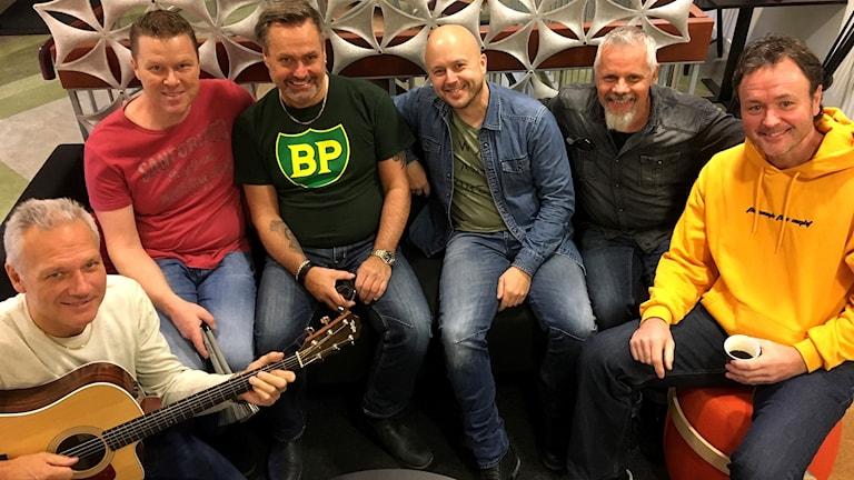 Bandmedlemmarna i Black Jack inklämda i radiohusets soffa. Foto: Ann-Charlotte Carlsson/Sveriges Radio