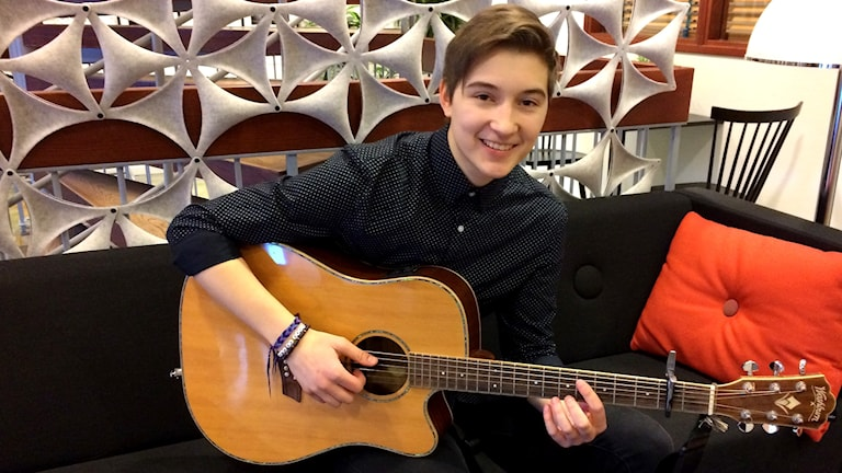 Hector Brännlund sitter med gitarr i soffa. Foto: Ann-Charlotte Carlsson/Sveriges Radio