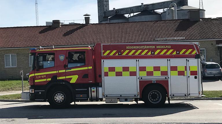 Brandbil utomhus vid fabrik.