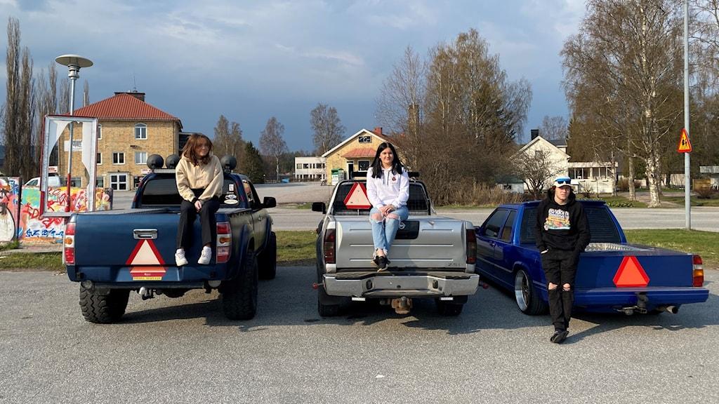 Bakänden på tre bilar, två tjejer och en kille står vid bilarna.
