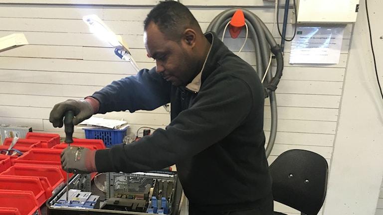 Musa Siraj skruvar i en dator på Återbruket i Bjästa.