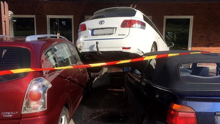 Bilen som körde ihjäl pojken står ovanpå motorhuven på två andra bilar på parkeringen. Foto: Gobiten.se