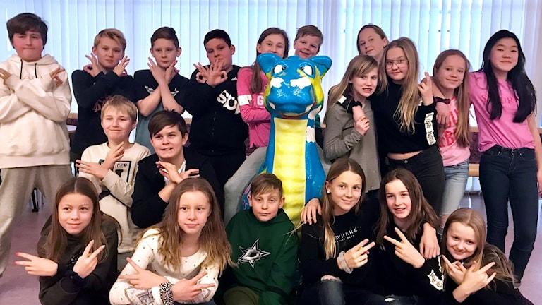 """Eleverna i 5B på Uslands skola står och sitter runt en """"Uslandsdrake"""". Foto: Marléne Jonsson"""