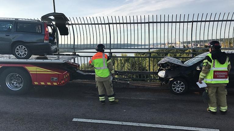 Bil på bärgningsbil och räddningspersonal på alnöbron.