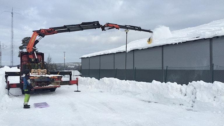 En stor snömaskin röjer tak från innebandyhallens tak på Skyttis.