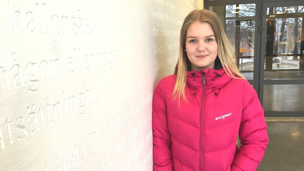 Molly Markusson står lutad mot en vit vägg.