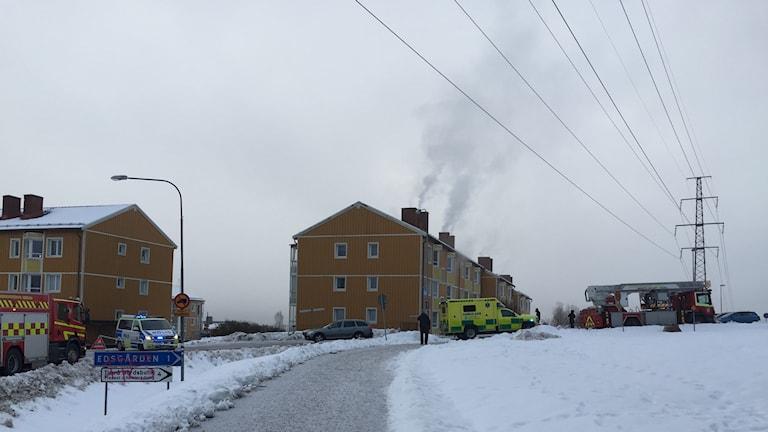 Bilden föreställer ett brunt lägenhetshus med tre våningar i Timrå. Utanför huset står en gul ambulans, en polisbil i blått, vitt och gult samt två röda brandbilar. Ur husets skorstenar stiger tjock rök mot den grå himlen. På marken runt om ligger snön.