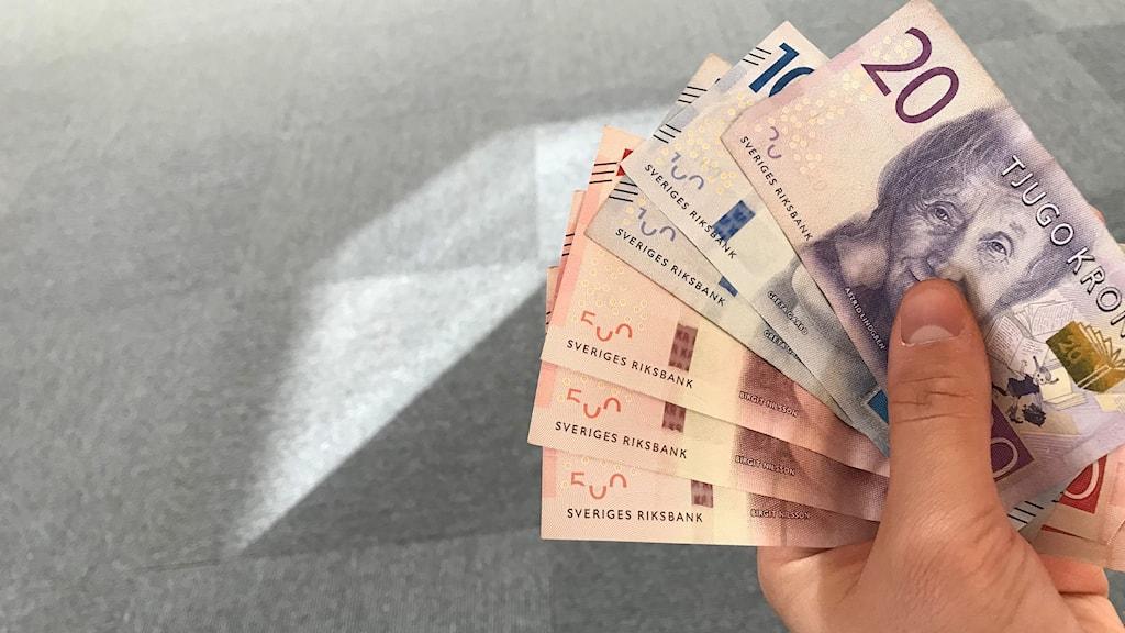 En hand håller i en bunt sedlar bestående av tre femhundra-lappar, två hundra-lappar och en tjugo-lapp. Foto: Alexander Arvidsson/Sveriges Radio