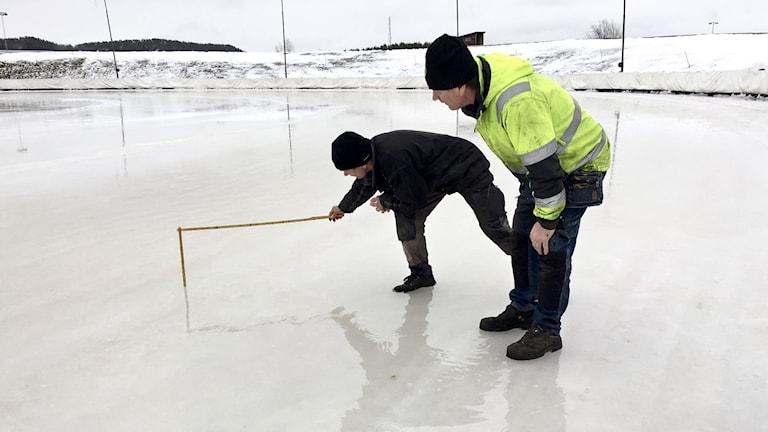 Två män står på isracingbana och mäter vattennivån med tumstock.