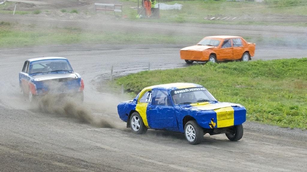 """Tre bilar synes köra på en slingrande grusbana, dammoln sprider sig över vägbanan. Bilarna är lappade och lagade, buckliga och med lös plåt. Den första bilen är målad i gult och blått, högst upp på fönsterrutan står """"Örnsköldsviks MK"""". Bakom den syns en blå bil med röda detaljer, och till sist en knallorange bil."""
