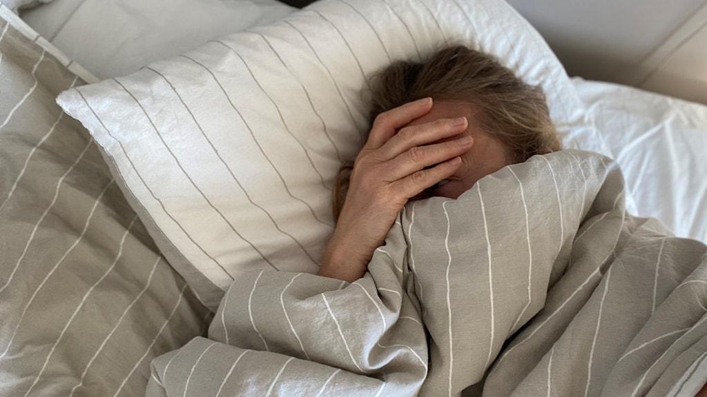 Huvud på kudde i sängen, handen över ansiktet.