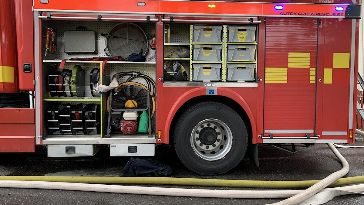 Sidan av en brandbil med släckningslangar kopplade.