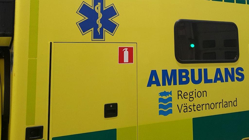 Del av sidan på en ambulans, skrapmärken i plåten längst upp mot taket.