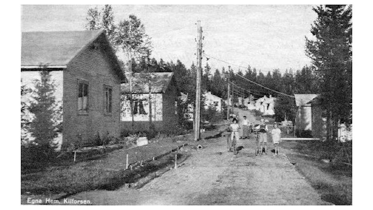 """Svart-vit bild på bygatan med """"egna hem"""" där några barn står mitt på vägen med cyklar. Foto: Bilddatabas Sollefteå Museum"""