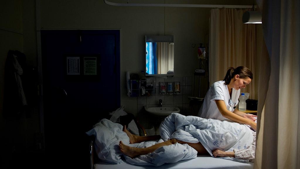 Sjuksköterska hjälper en patient som ligger i en säng på en vårdsal.