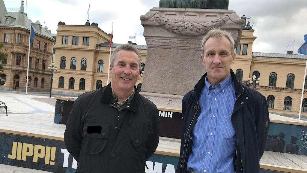 Två män står vid ett ödsligt torg