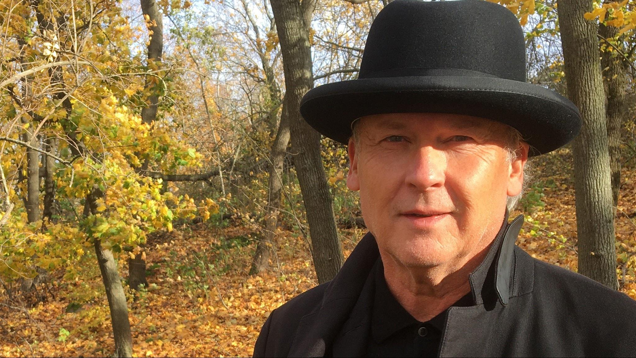 Författaren Klas Östergren, porträttfoto ute i höstfärger. Klas bär hatt.