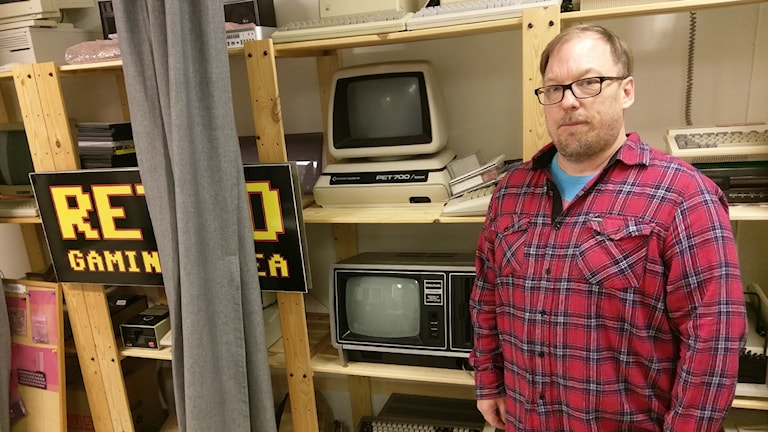 Michael Berglund från Retrogathering framför en hylla med gamla spelkonsoler.