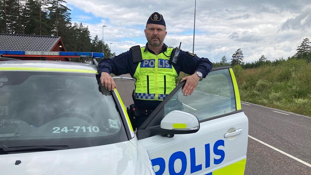 Man i polis uniform står vid polisbil och tittar in i kameran.