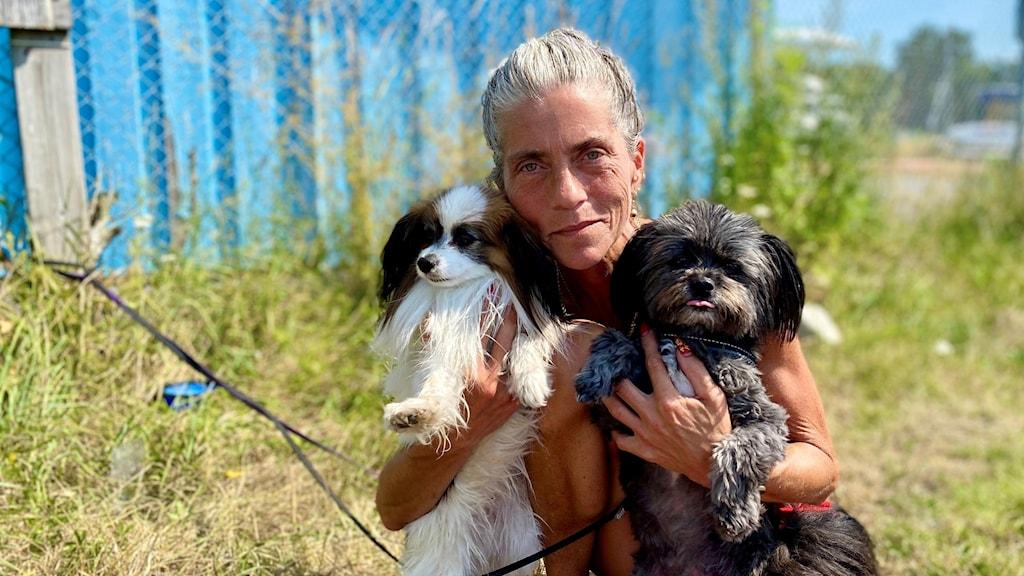 En kvinna håller upp sina två hundar mot ansiktet och tittar in i kameran.