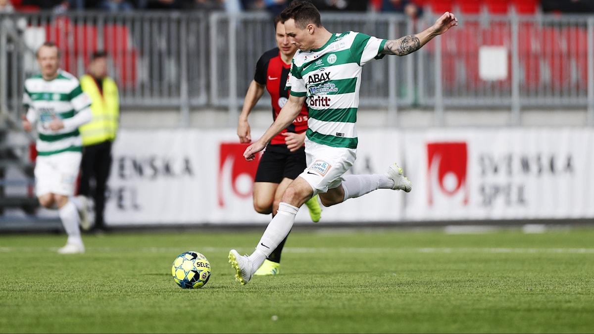 En fotbollsspelare som just ska sparka till bollen, han har vita byxor och grön och vitrandig tröja. Bakom honom en motspelare i rött och svart.