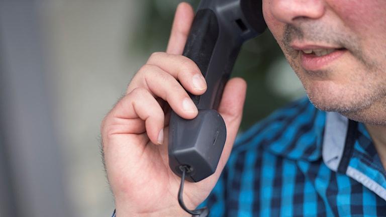 Man talar i telefon.