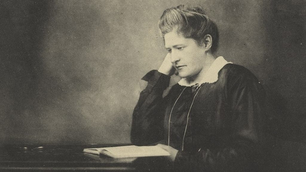 En kvinna som sitter vid ett bord med en bok.