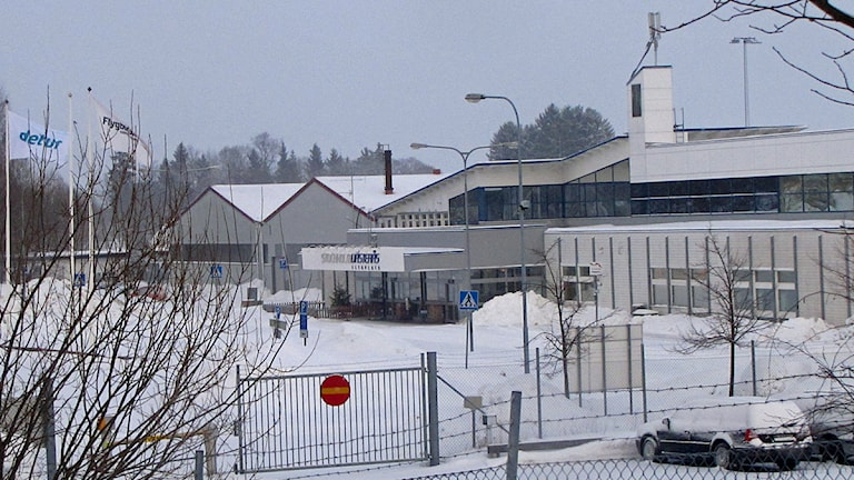 Entrésidan Västerås flygplats. I förgrunden staket och bilparkering. Foto: Camilla Olsson/SR.