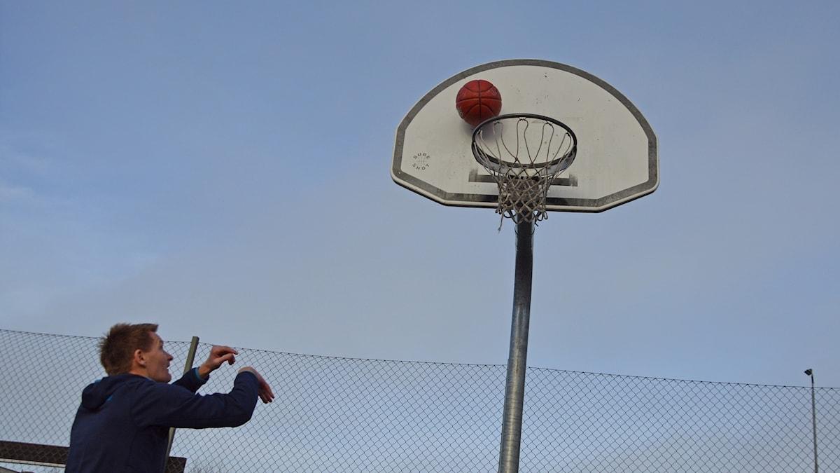 Kastar basketboll i korgen.