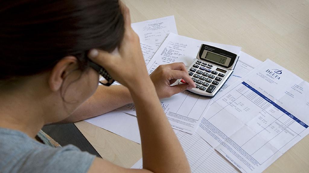 En skuldsatt kvinna sitter lutar över sina räkningar. Foto: Claudio Bresciani/Scanpix.