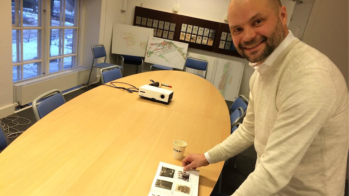 Kai Pasma, vd på The Steam Hotel, bläddrar i en bok med bilder av arbetare på Ångkraftverket.
