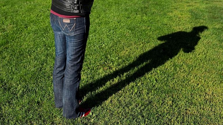 Flicka står på gräsmatta