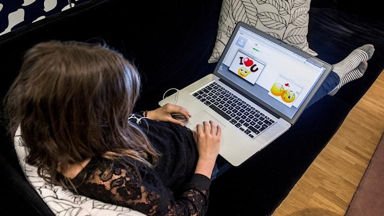 En ung flicka tittar på en datorskärm.