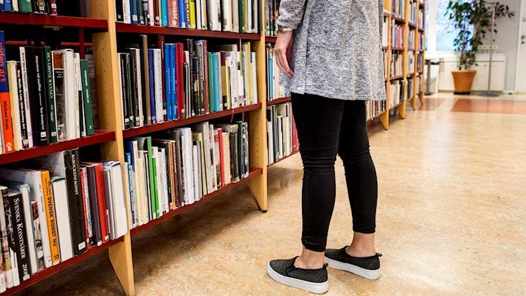 Kvinna letar efter böcker på bibliotek