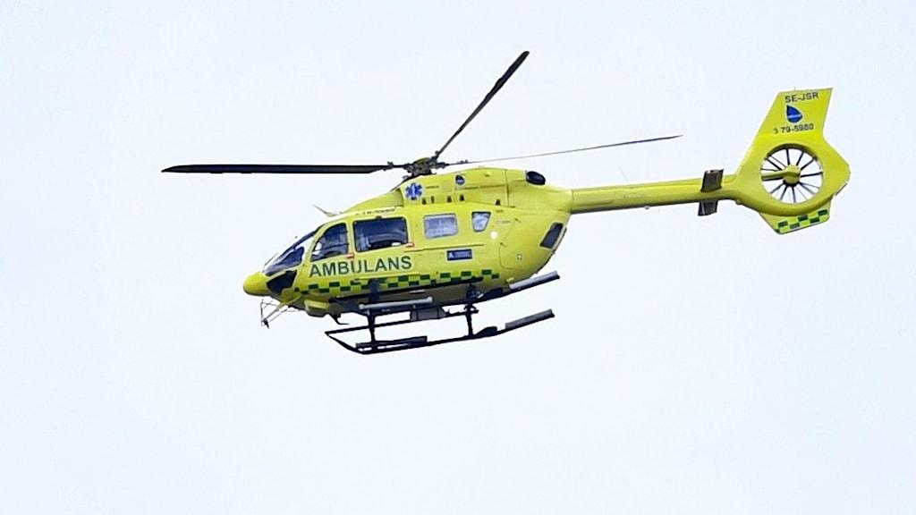 En gul helikopter med orden ambulans.