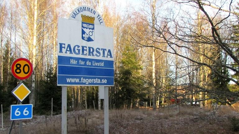 """Fagerstas kommunskylt med slogan """"Här får du livstid"""" och kommunvapen."""