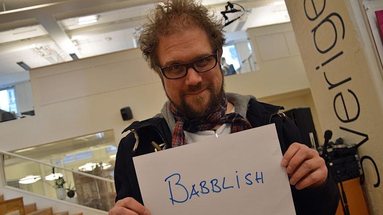 """Dan Linder håller upp ett papper med texten """"Babblish"""". Foto: Monica Elfström/Sveriges Radio."""