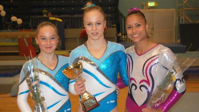 Jonna Adlerteg i mitten, tillsammans med medaljörerna Emma Larsson och Marcela Torres. Foto: Gymnastikförbundet.