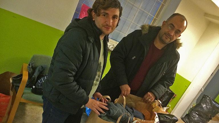 Ahmad Mujawaz och Ayad Awini från Syrien visar papperskassar med insamlade kläder. Foto: Monica Elfström/Sveriges Radio.