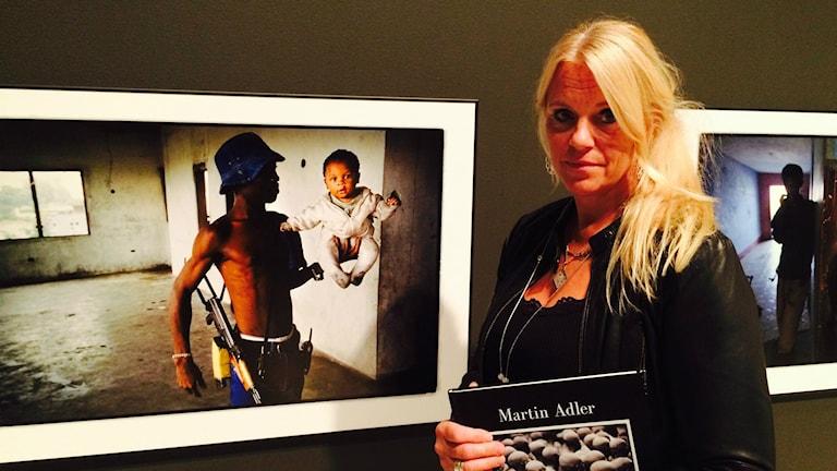 Katarina Adler framför sin bortgångne makes bild. Foto:Terje Lund/Sveriges Radio
