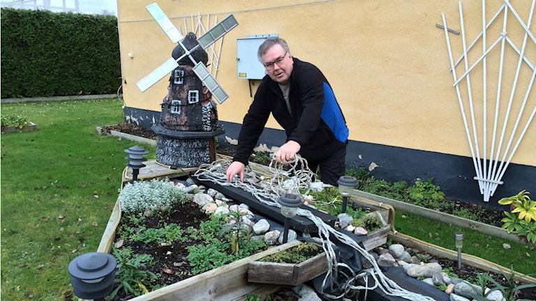 Sivert Horneman bygger ett konstgjort vattenfall med några blinkade ljusslingor. Foto: Martin Vare/Sveriges Radio