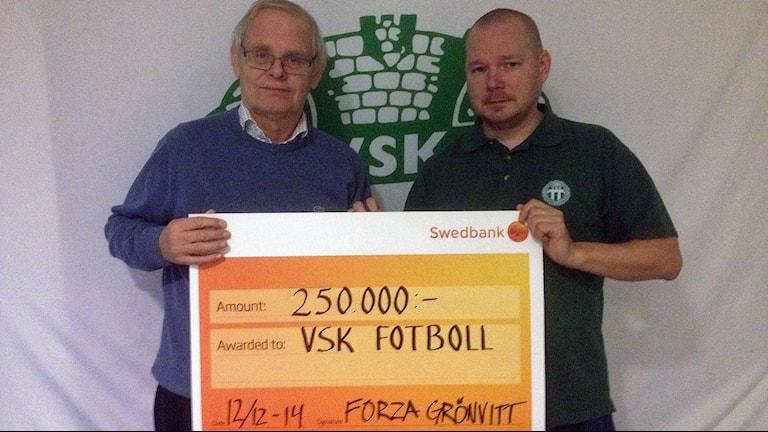Forza Grönvitts ordförande Daniel Blomberg lämnar över en kvarts miljon till VSK Fotboll. Foto: Johan Bengts/SR.