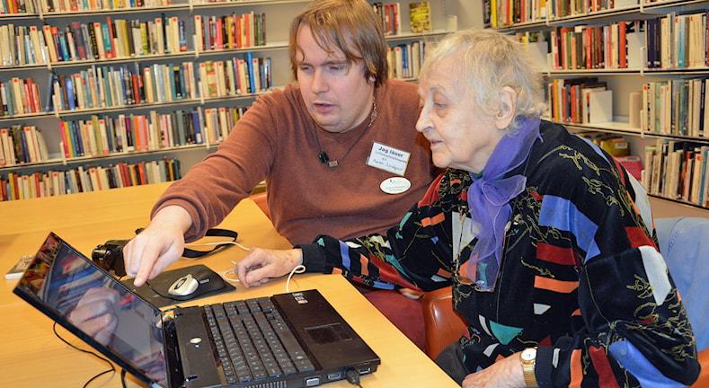 Andreas Pettersson, it-bibliotekarie, hjälper Hagar Söderholm, 84, med datorn. Foto: Monica Elfström/Sveriges Radio.
