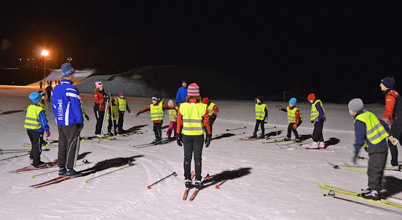 Barn med skidor och reflexvästar samlade vid elljusspåret. Foto: Monica Elfström/Sveriges Radio.
