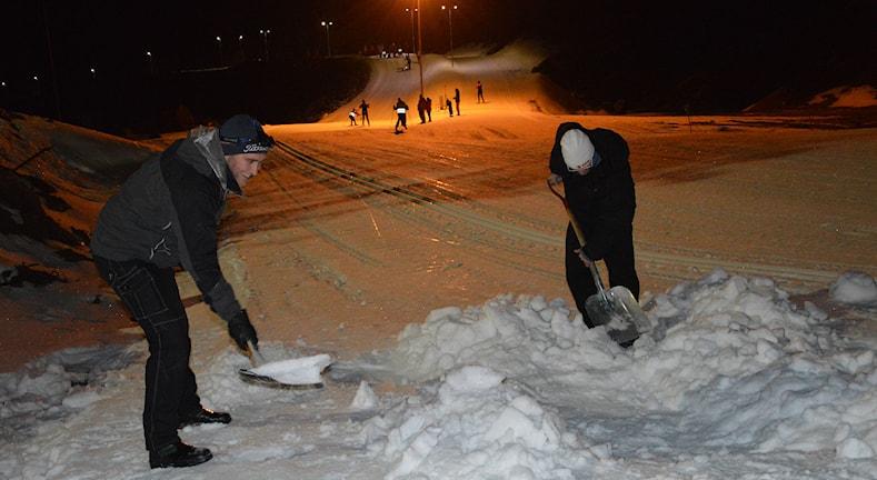 Två män skottar snö, i bakgrunden elljusspår. Foto: Monica Elfström/Sveriges Radio.