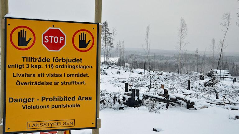 """Länsstyrelsens varningsskylt med text""""tillträde förbjudet"""" i svartbränt skogslandskap med snötäcke. Foto: Monica Elfström/Sveriges Radio."""