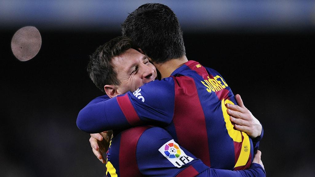 Männen kramas däremot friskt i sportsammahang. Här Barcelonas Lionel Messi och Luiz Suarez Foto: Manu Fernandez/TT Nyhetsbyrån