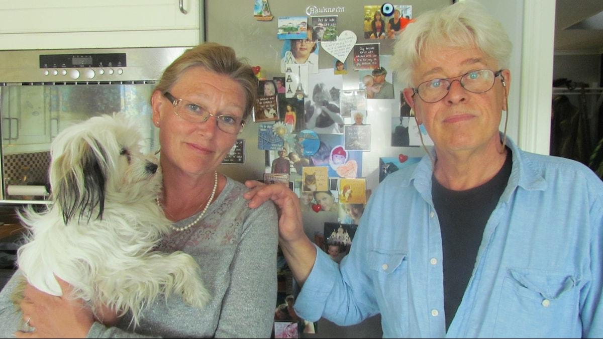 Christina och Gert Fredrixon framför kylskåpet med ett collage av bilder på Beatrice som liten. Foto: Helena Lund/SR.