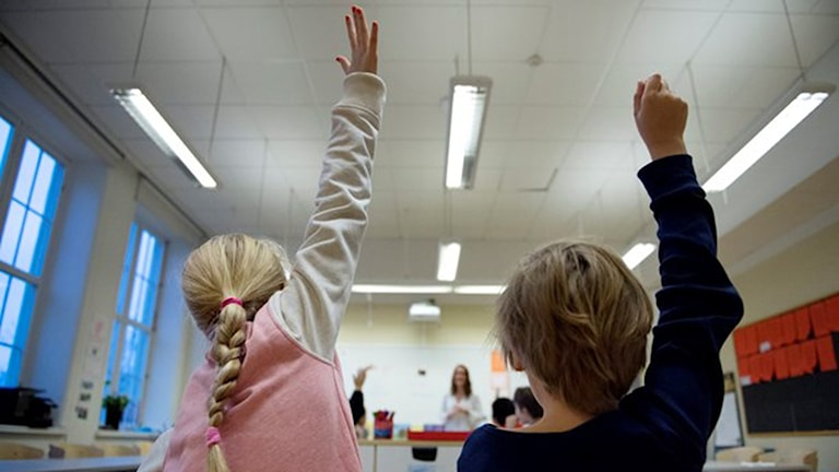 På bilder ser vi två elever, bakifrån, som sitter i ett klassrum och räcker upp handen.